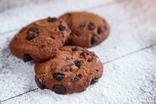 Zandkoekkoekjes met chocoladeschilfers op houten die met poedersuiker worden bestrooid. vers gebak. havermoutkoekjes voor ontbijt. selectieve aandacht.