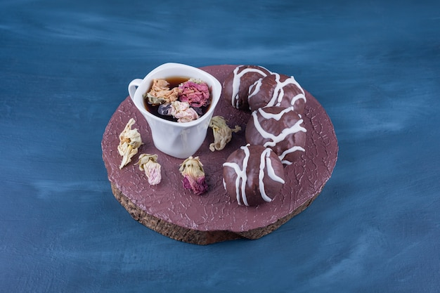 Zandkoekkoekjes omhuld met witte en donkere chocolade met een glazen kopje thee.
