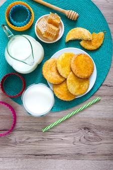 Zandkoekmelkkoekjes op een bord, melk en honing.