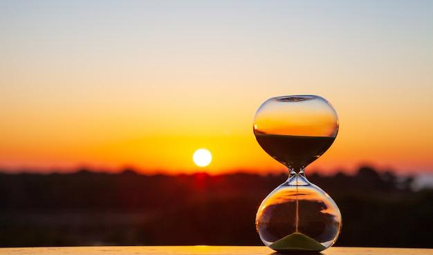 Zandloper bij zonsondergang of zonsopgang op een wazige achtergrond, als herinnering aan de tijd die voorbijgaat