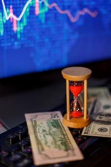 Zandloper en dollars op het toetsenbord op de achtergrond van grafieken