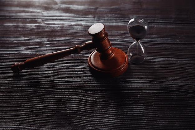 Zandloper en houten rechter hamer op een tafel