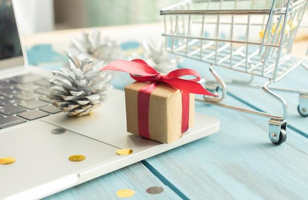 Zandloper en kleine geit met dozen met kerstcadeaus op de achtergrond van een laptop