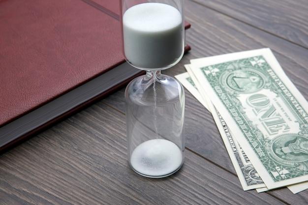 Zandloper, geld en notitieboekje liggen op tafel. zakelijke kantoorartikelen. tijd is geld. zakelijke oplossingen op tijd.