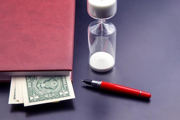 Zandloper, geld, pen en notitieboekje liggen op tafel. zakelijke kantoorartikelen. tijd is geld. zakelijke oplossingen op tijd.