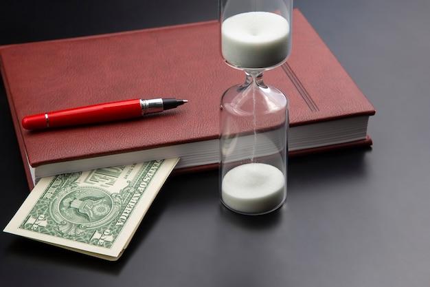 Zandloper, geld, pen en notitieboekje liggen op tafel. zakelijke kantoorartikelen