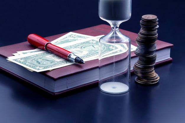 Zandloper, geld, pen en notitieboekje liggen op tafel.