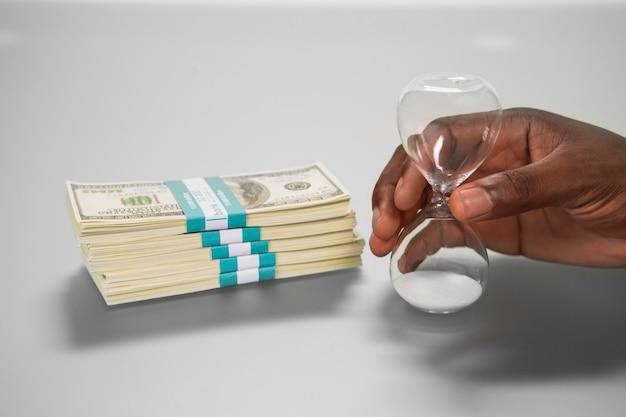 Zandloper in de buurt van geldpakket. begin met aftellen. kostbare dingen. let op uw keuze.