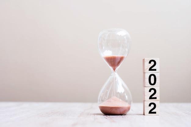 Zandloper met 2022 houten kubusblokken op tafel, zand stroomt door de bol van sandglass en meet de verstrijkende tijd. aftellen, deadline, gelukkig nieuwjaar, resolutie en nieuw startconcept