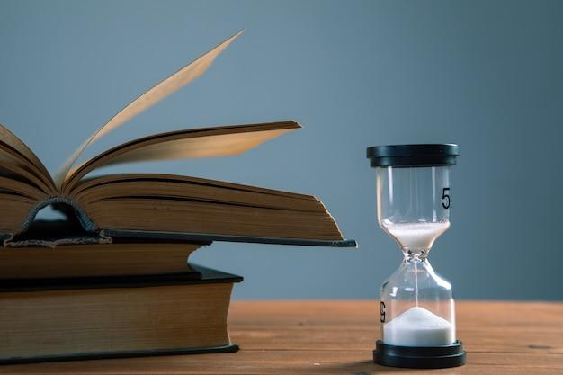 Zandloper met boeken op tafel
