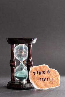 Zandloper met de tijd omhoog tekst op zwart oppervlak