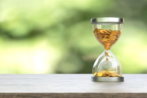 Zandloper met gouden munten op onscherpte tijd is geld concept