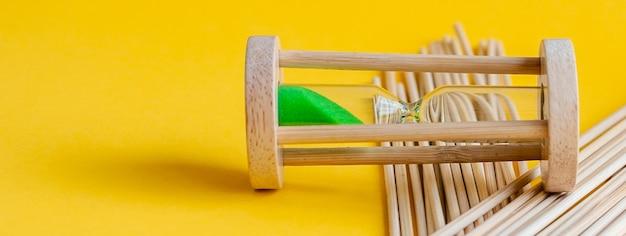 Zandloper met groen zand binnen op een gele achtergrond