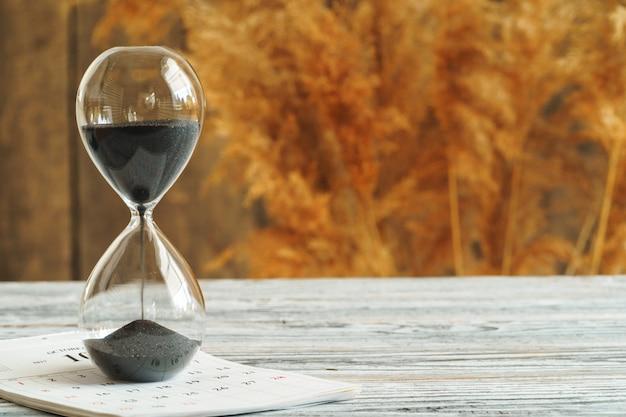 Zandloper met kalender op houten bureau. tijd concept