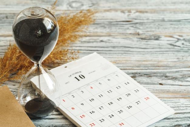 Zandloper met kalender op houten bureau