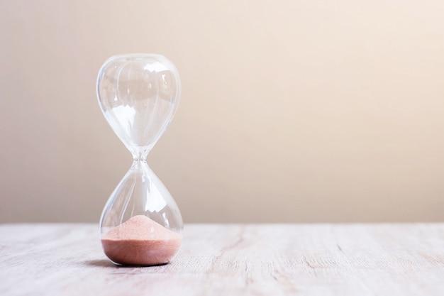 Zandloper op tafel, zand stroomt door de bol van sandglass en meet de tijd die voorbijgaat. countdown, deadline, levensduur en pensioen concept