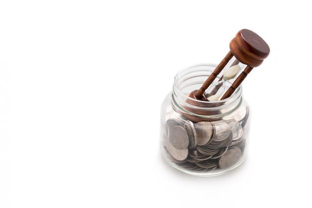 Zandloper op veel munten in een glazen pot