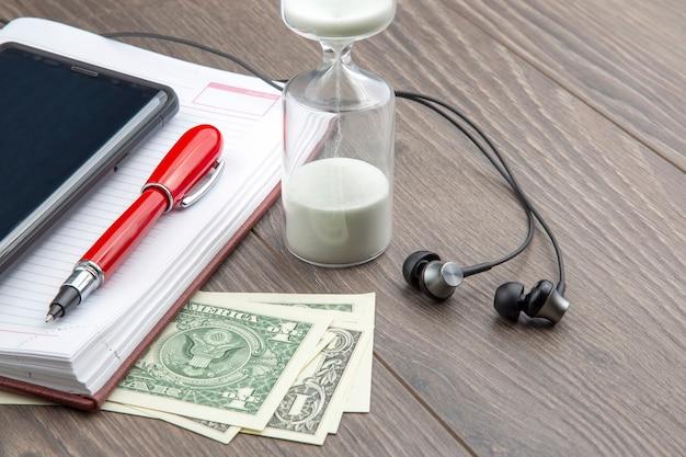 Zandloper, pen, notitieboekje, geld en oortelefoons liggen op tafel. zakelijke kantoorartikelen. tijd is geld. zakelijke oplossingen op tijd.