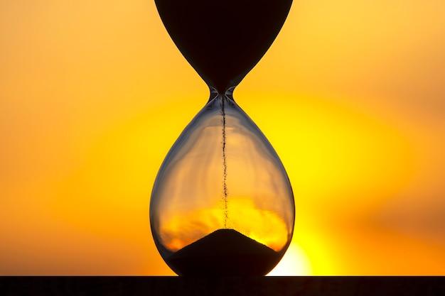 Zandloper telt de tijdsduur tegen de achtergrond van de avondzon