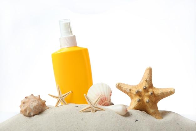 Zandschelpen zeester en zonnebrandcrème geïsoleerd op wit