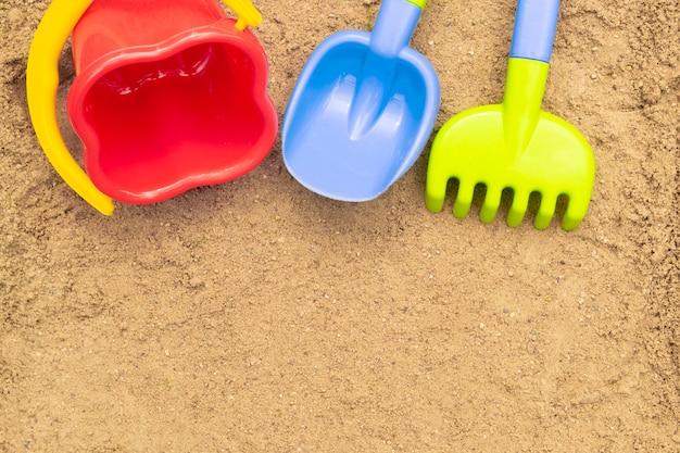 Zandspeelgoed voor kinderen: schep, hark en emmer. zandbak buiten. zomer concept. met plaats voor tekst.
