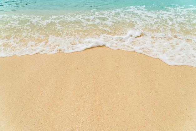 Zandstrand kust met blauwe golf en wit schuimend van blauwe zee in de zomer.