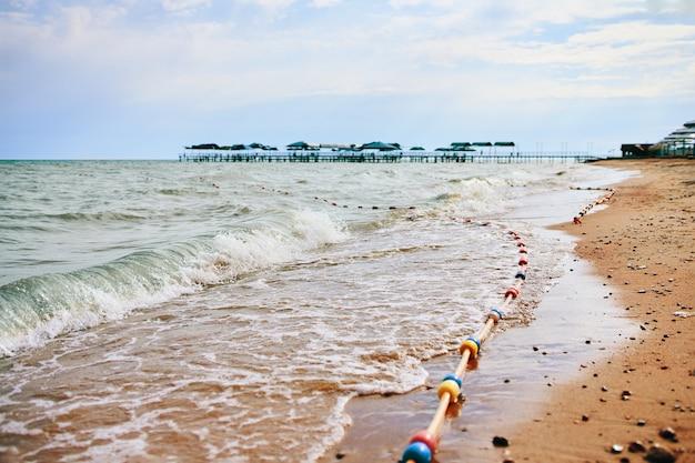 Zandstrand met golven van de zee.