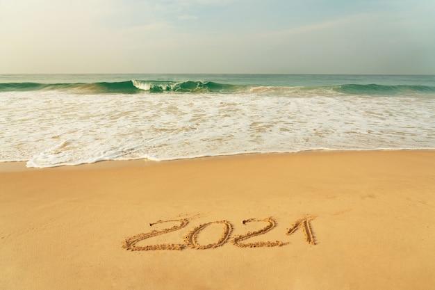 Zandstrand met nieuwjaar symbool 2021 en blauwe golven, sri lanka.