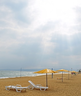 Zandstrand met parasols, ligstoelen. zonder mensen