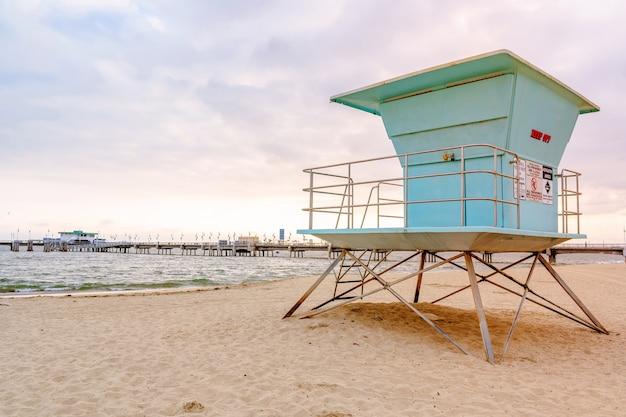 Zandstrand op het strand in los angeles blauwe torens van strandwachten bij zonsondergang aan de kust van californië