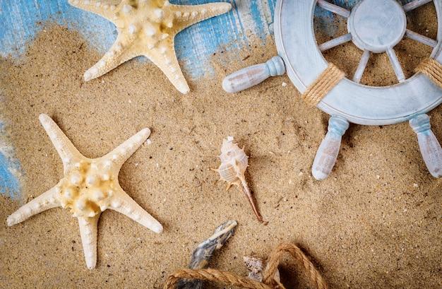 Zandstrand op oude blauwe houten achtergrond op decoratieve stuurwiel met zeester, schelpen