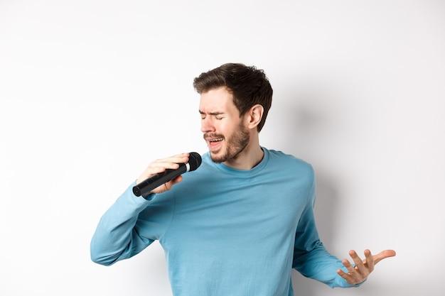 Zanger die lied op witte achtergrond uitvoert. jonge man zingen in de microfoon op karaoke.