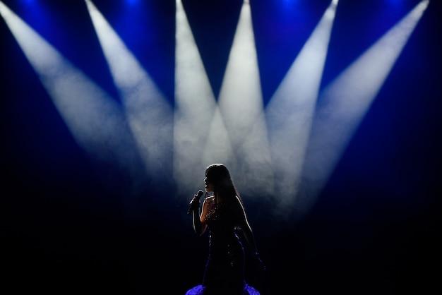 Zanger in silhouet. een jonge vrouw zangeres op het podium tijdens een concert.