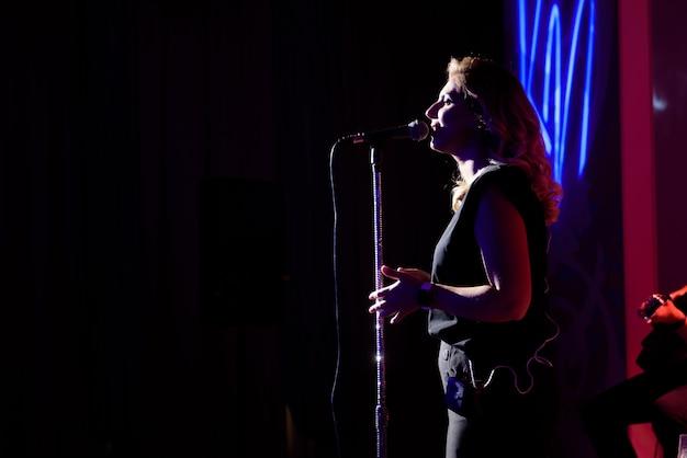 Zangeres, die haar vocale geluid uitvoert. met lensflare en spotlight.