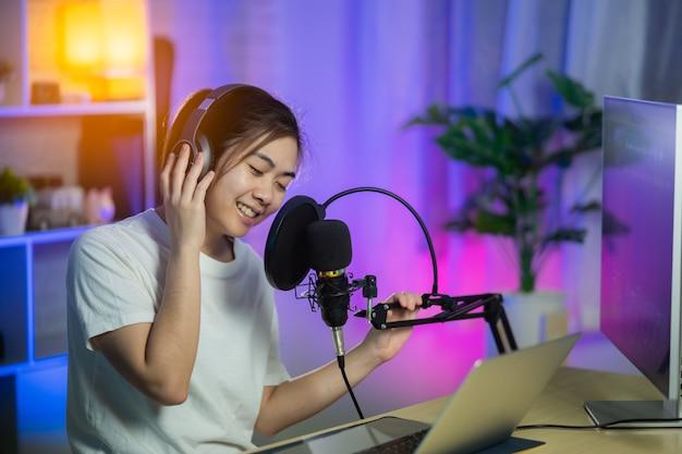 Zangeres die zingen met een koptelefoon die een nieuw nummer opneemt in de thuisopnamestudio