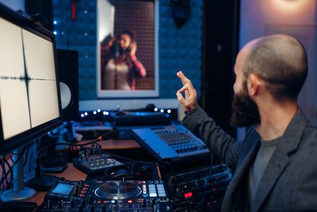 Zangeres in de opnamekamer en geluidstechnicus en op afstandsbedieningspaneel in de studio.