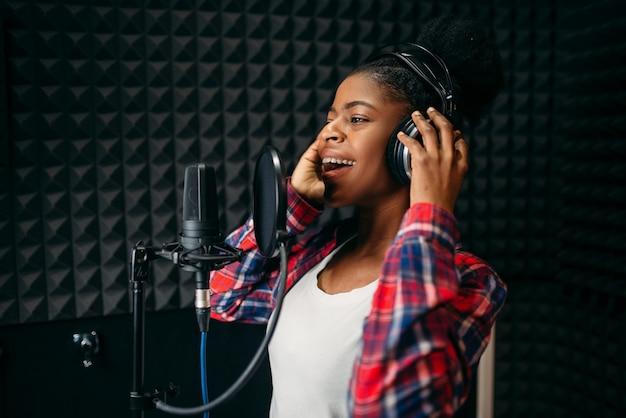 Zangeres in hoofdtelefoons liedjes in audio-opnamestudio.