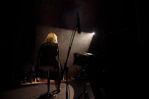 Zangeres met haar band die op het podium presteert. concert. uitzicht vanuit het auditorium.