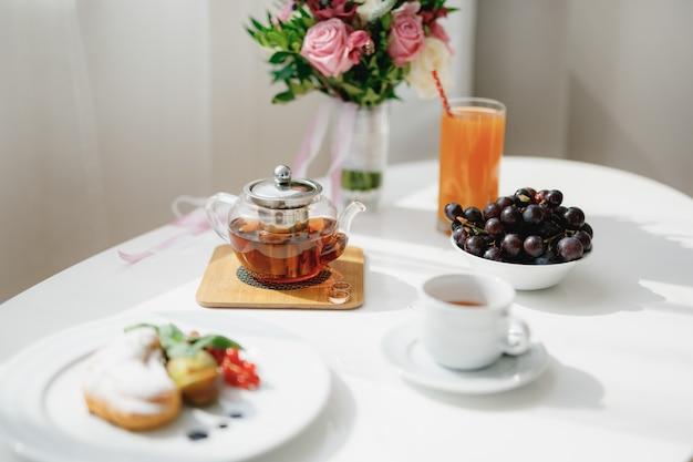 Zavrnik met thee op een houten standaard met trouwringen op een witte tafel met een bord, kop en kom