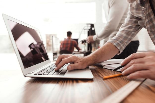 Ze controleren de schriftgeleerden van de 3d-printer op de laptop