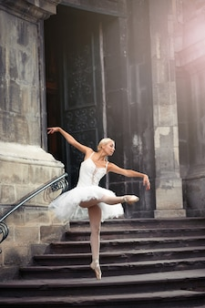 Ze ging op zoek naar inspiratie. volledig portret van een ballerina die sierlijk danst in de buurt van een oud huis old