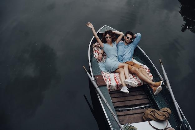 Ze hebben liefde gevonden. bovenaanzicht van mooie jonge paar omarmen terwijl liggend in de boot