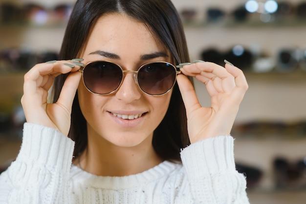 Ze heeft haar keuze gemaakt. mooie jonge vrouw die haar nieuwe zonnebril aanpast en glimlacht terwijl hij in optische opslag staat