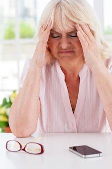 Ze heeft hulp nodig. depressieve oudere vrouw die het hoofd in de handen houdt en de ogen gesloten houdt terwijl ze aan tafel zit met een mobiele telefoon erop
