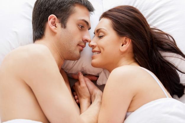 Ze houden van elkaar. bovenaanzicht van mooie jonge verliefde paar liggend in bed en hand in hand