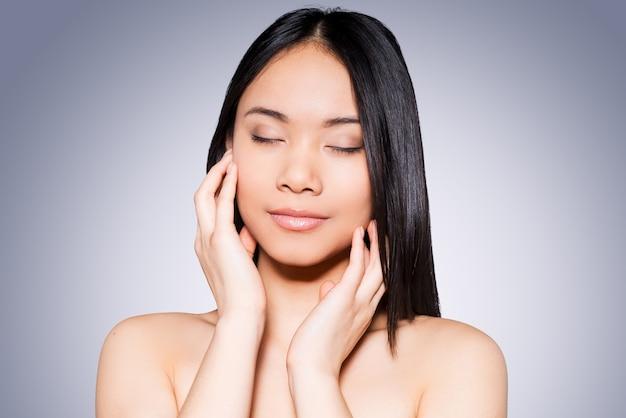 Ze houdt van haar frisse huid. portret van een mooie jonge en shirtloze aziatische vrouw die haar gezicht aanraakt terwijl ze tegen een grijze achtergrond staat