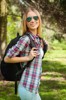 Ze houdt van wandelen. mooie jonge vrouw die haar rugzak draagt en naar de camera kijkt terwijl ze in de natuur staat