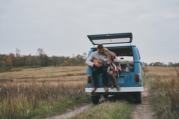 Ze is zijn muze. knappe jongeman gitaarspelen voor zijn mooie vriendin zittend in de kofferbak van blauwe retro-stijl minibusje