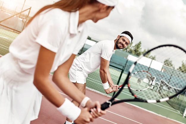 Ze spelen als een team mooie jonge vrouw die een tennisracket vasthoudt en wegkijkt terwijl