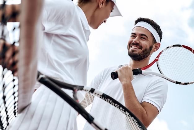Ze spelen als een team, mooie jonge vrouw en man die een tennisracket vasthouden en discussiëren